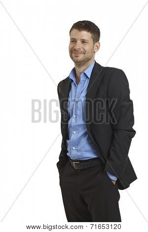 Young businessman smiling with hands in pockets, looking away.