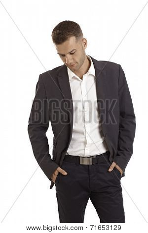 Young businessman thinking, standing with hands in pockets.