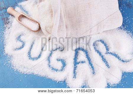 Inscription sugar made of white granulated sugar on color wooden background