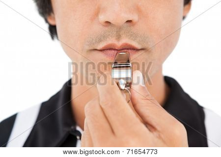 Close up mid section of referee blowing whistle on white background