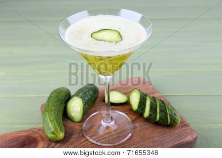 Cucumber cocktail on cutting board on wooden background