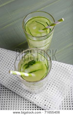 Two glasses of cucumber cocktail on napkin on wooden background