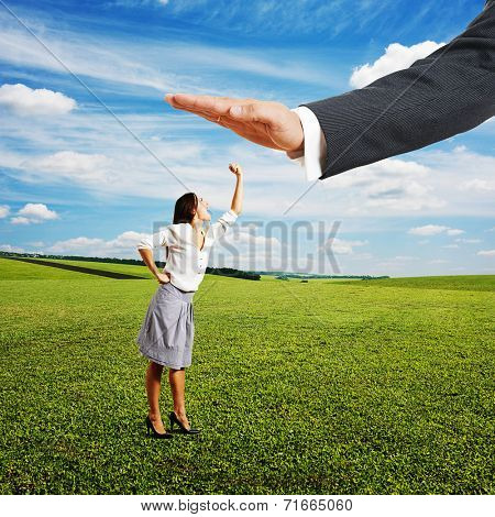 concept photo of conflict between subordinate and boss. displeased businesswoman looking up at big palm of his boss, screaming and showing her fist. bright photo at outdoor