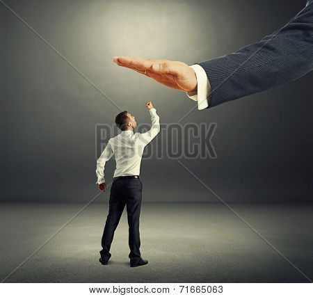 concept photo of conflict between subordinate and boss. dissatisfied businessman looking up at big palm of his boss and showing in the dark room
