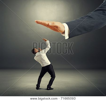 concept photo of conflict between subordinate and boss. frightened businessman looking up at big palm of his boss over dark background