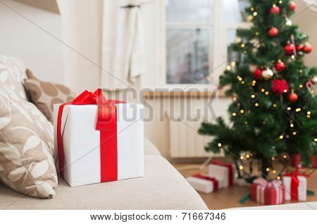 christmas, x-mas, holidays, winter and happiness concept - gift box on coach at home
