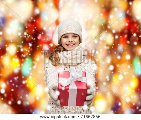 christmas, xmas, happiness concept - smiling girl in hat, muffler and gloves with gift box
