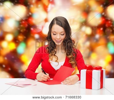 christmas, holidays, celebration, greeting and people concept - smiling woman with gift box writing letter or sending post card over red lights background