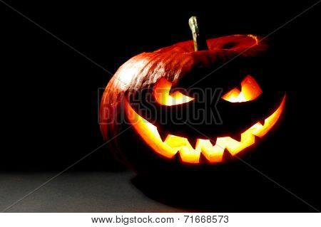 Scary smiling Halloween pumpkin on dark background