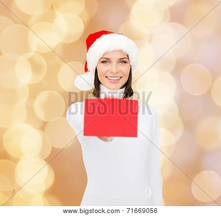 christmas, holdays, people, advertisement and sale concept - happy woman in santa helper hat with blank red card over beige lights background