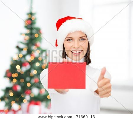 christmas, holdays, people, advertisement and sale concept - happy woman in santa helper hat with blank red card showing thumbs up gesture over living room and christmas tree background