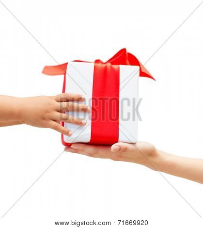 holidays, present, christmas, childhood and happiness concept - close up of child and mother hands with gift box