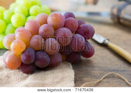 Harvest season. Fresh harvested red, black and white (green) grapes on a table.
