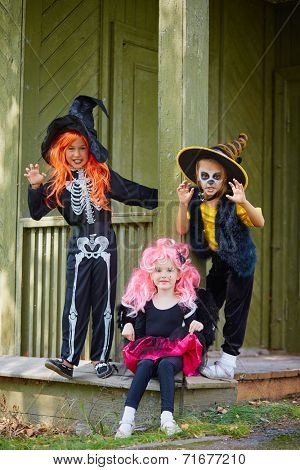 Group of Halloween girls posing on the porch of dilapidated house