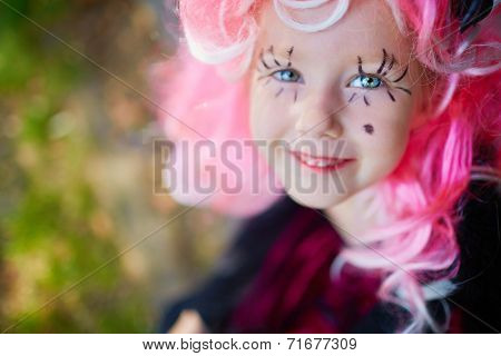 Cute girl with painted eyelashes and pink wig looking at camera with smile