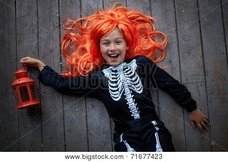 Portrait of joyful girl in red wig holding lantern and looking at camera