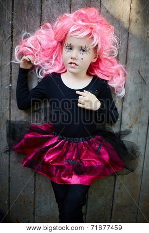 Calm Halloween girl with pink hair looking at camera