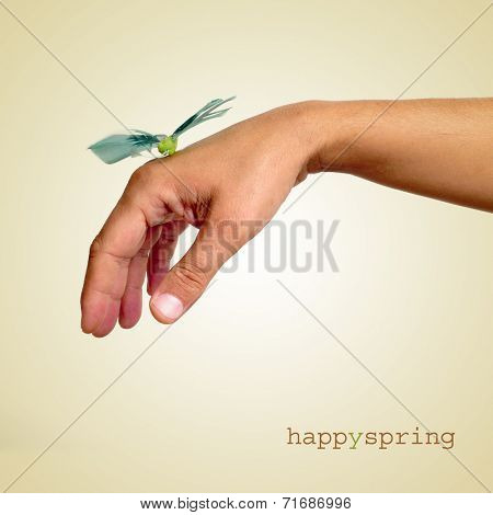 a fake butterfly landed in the hand of a young man and the sentence happy spring on a beige background