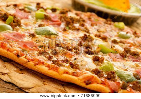 closeup of a pizza with ground beef, ham, onion and green pepper