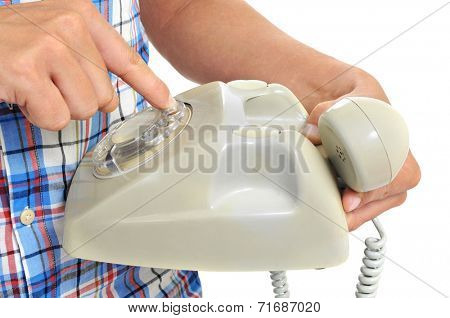 detail of a young man dialing in a rotary dial telephone