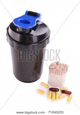 Whey protein powder in scoop with vitamins and plastic shaker isolated on white