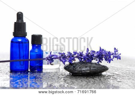 a bunch of lavender flower with oil and stone on wet background