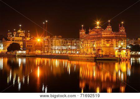 Sikh sacred site gurdwara Sri Harmandir Sahib (also known as The Golden Temple, also Darbar Sahib) illuminated at night. Amritsar, Punjab state, India