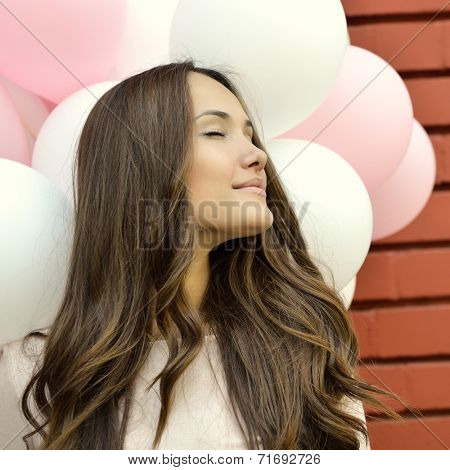 Happy young woman standing over red brick wall and holding pink and white balloons. Pleasure. Dreams. Image toned.