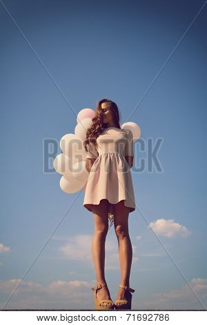 Fashion girl with  air balloons over blue sky, image toned.