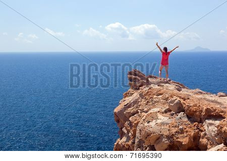 Happy woman on the rock with hands up. Winner, success, active, travel concepts. Santorini island, Greece. Winner, success, active, travel concepts