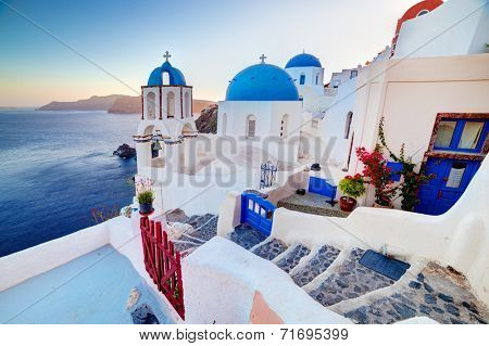 Oia town on Santorini island, Greece at sunset. Traditional and famous churches with blue domes over the Caldera, Aegean sea