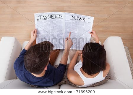 Couple Reading Newspaper Together On Sofa