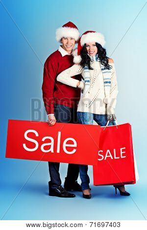 Full length portrait of a happy young people standing with a lot of shopping bags. Sale.