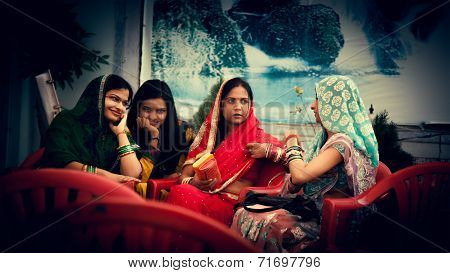 Happy Indian womens talking in colourful sarees