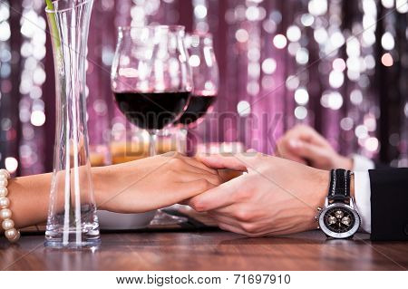 Couple Holding Each Other's Hand At Dinner