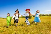 picture of happy halloween  - Group of four kids about 7 years old running in the autumn field in Halloween costumes - JPG