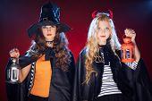 stock photo of antichrist  - Halloween girls in black cloaks holding lanterns - JPG