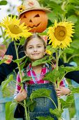 image of scarecrow  - Scarecrow and happy girl  in the garden  - JPG
