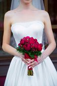 stock photo of wedding feast  - Bride holding a wedding bouquet of red roses - JPG