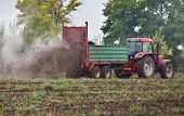 stock photo of tractor trailer  - Tractor with trailer fertilizing field with natural manure - JPG