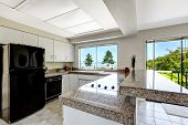 image of granite  - White kitchen room with black appliances and granite tops - JPG