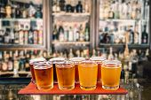 picture of draft  - Beer flight of eight sampling glasses of craft beer on a serving board in a bar - JPG
