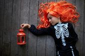 foto of warlock  - Portrait of cute girl in red wig and Halloween costume - JPG