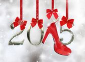 stock photo of shoe  - High heel shoe and 2015 number hanging on red ribbons in a glittery background - JPG
