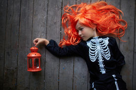 stock photo of antichrist  - Portrait of cute girl in red wig and Halloween costume - JPG