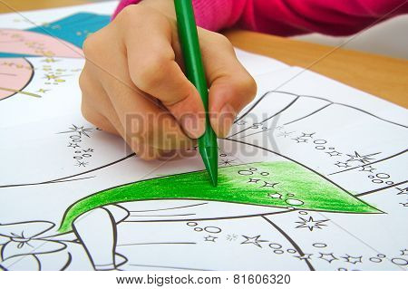Girl drawing with a green crayon in classroom. School concept.