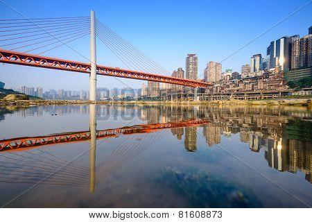 Chongqing, China cityscape at the Jialing River and Qianximen Bridge.