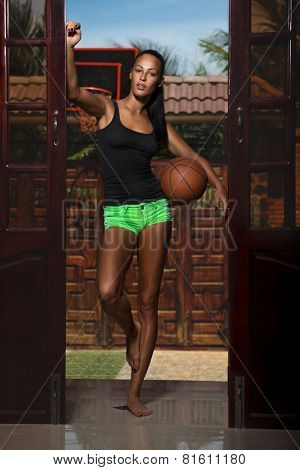 Woman with basket ball at home
