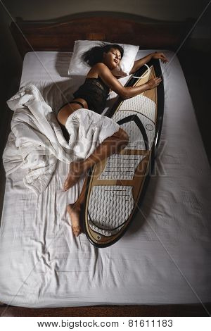 Surfer girl sleeping in bed