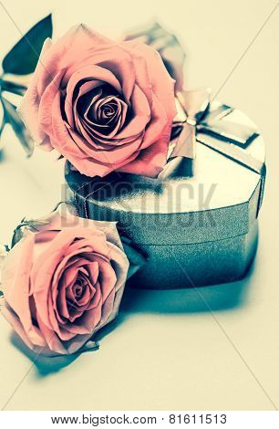 Close up of pink roses placed on a heart-shaped gift box. A vintage photo treatment.